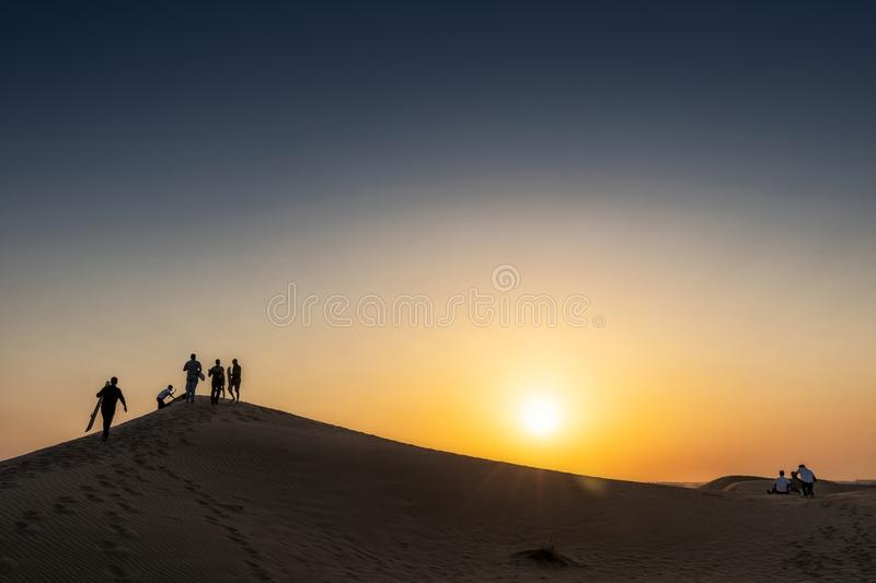 Group of friends having fun in the desert of Abu Dhabi on top of a dune to surf sand with sunset. Uae royalty free stock images