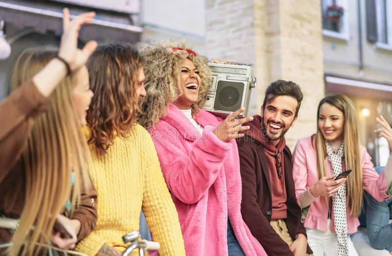 Group friends having fun listening music with vintage boombox - Happy young people making party in city outdoor royalty free stock photo