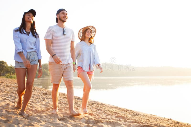 Group of friends having fun running down the beach royalty free stock photography