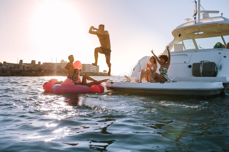 Group of friends having a great summer vacation. Young men diving into the sea from yacht with friends cheering. Group of friends having a great summer vacation stock images