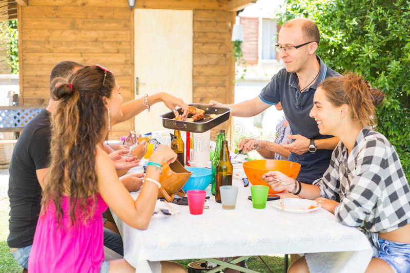 Group of friends having lunch together in the garden stock image
