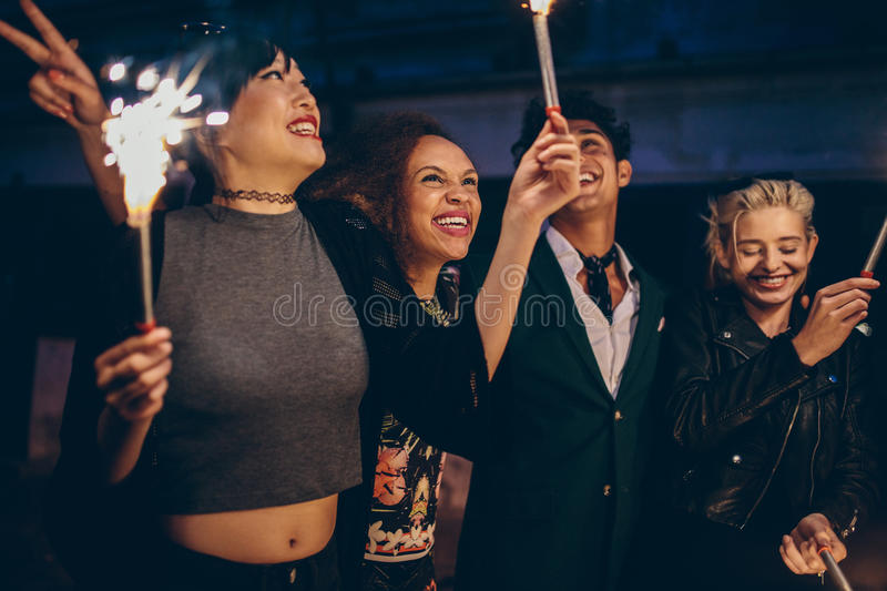 Group of friends having night party with sparklers. Young friends holding sparklers out on street at night. Group of men and women having night party with stock images