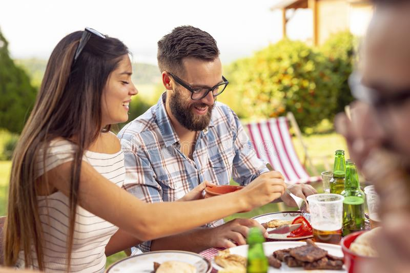 Barbecue party. Group of friends having an outdoor barbecue lunch, eating grilled meat, drinking beer and having fun stock image