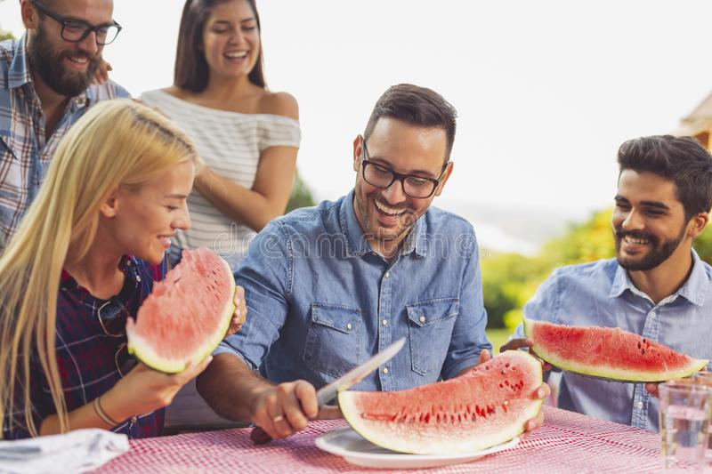 Man cutting watermelon slices. Group of friends having an outdoor lunch, eating fresh watermelon slices and having fun stock photo
