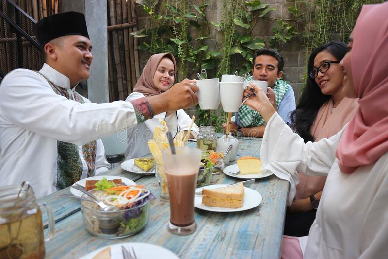 Group of friends having tea toast at table dining during ramadan royalty free stock photography