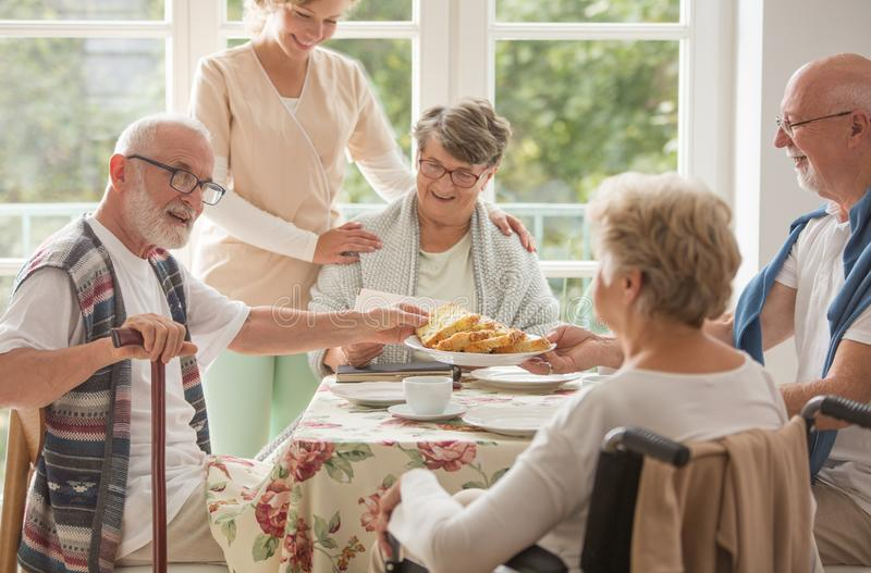 Group of friends with helpful carer sitting together at the table at nursing home dining room and eating cake. Group of senior friends with helpful carer sitting stock image