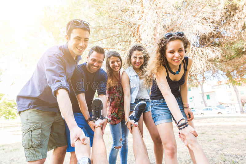 Group of friends helping someone to rise royalty free stock images