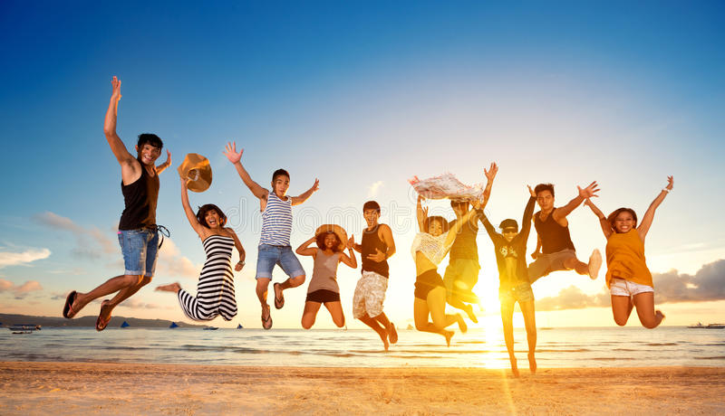 Group of friends jumping on beach royalty free stock photography