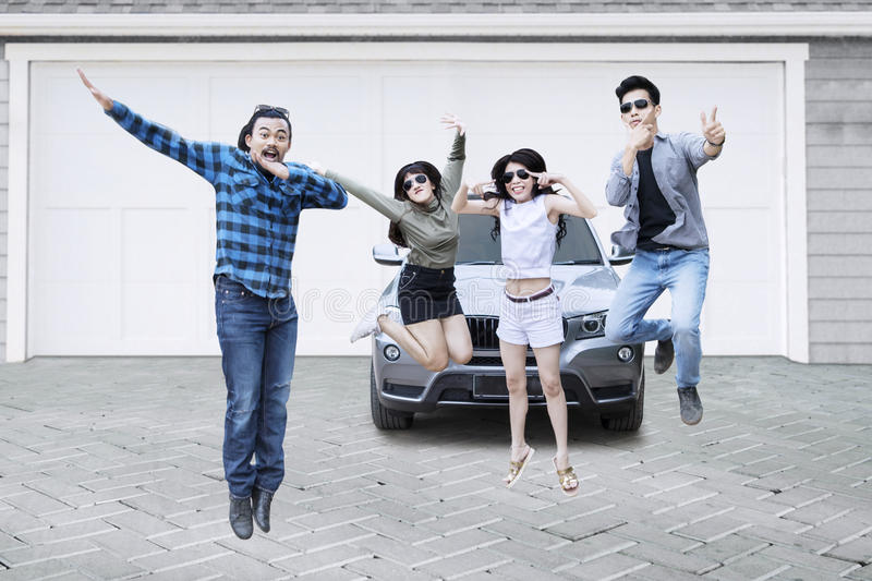 Group of friends jumping on garage. Multi ethnic group of friends wearing sunglasses, jumping together on the garage stock image