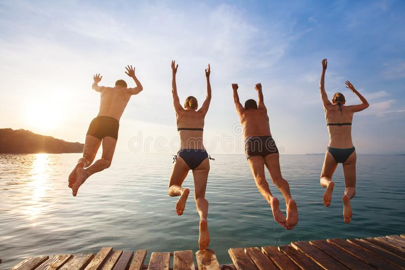 Happy beach holidays, group of friends jumping to water royalty free stock images