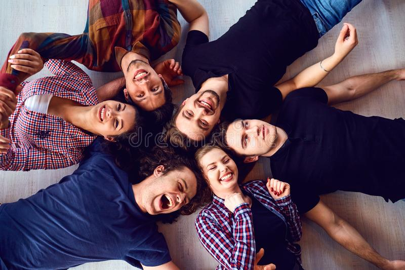 A group of friends are laughing lying on the floor in room. stock photography