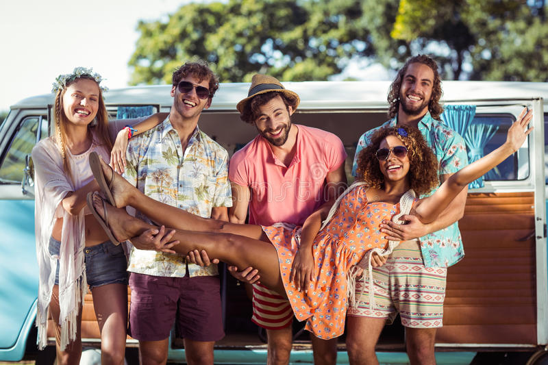 Group of friends lifting woman near campervan. In park royalty free stock photography