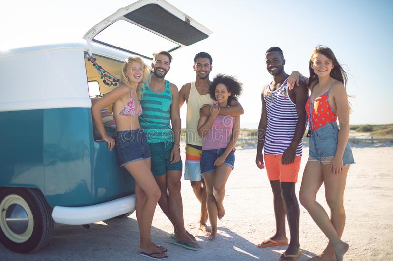 Group of friends looking at camera while standing near camper van at beach. Front view of happy group of diverse friends looking at camera while standing near stock photo