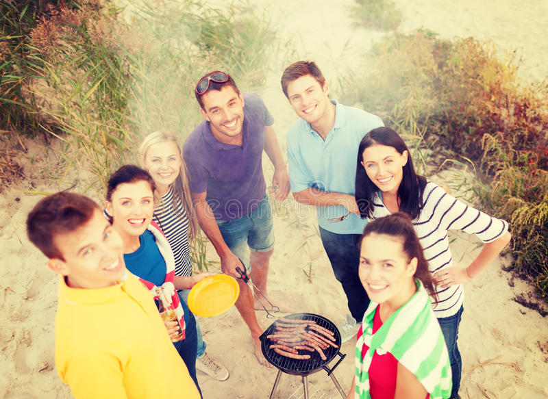 Group of friends making barbecue on the beach stock images