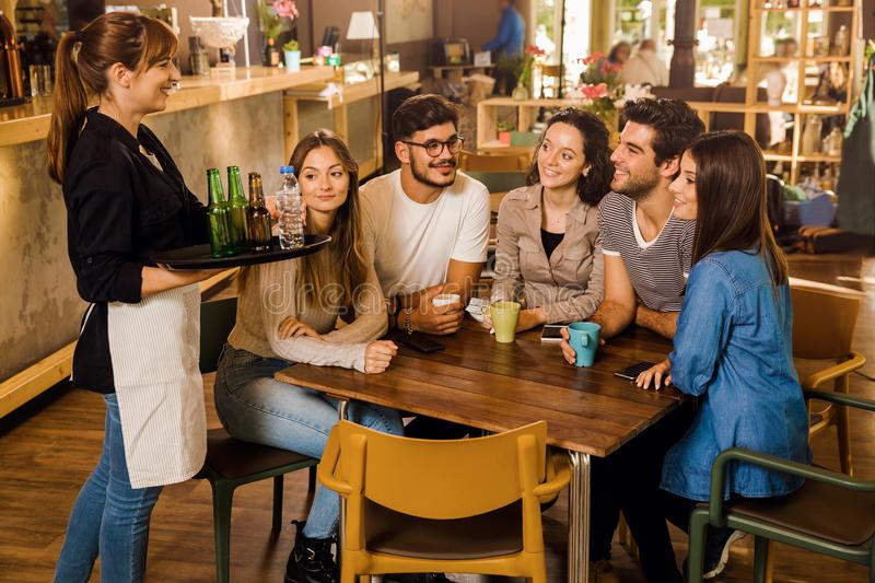 Talking to the waitress. A group of friends making a order at cafe royalty free stock photos