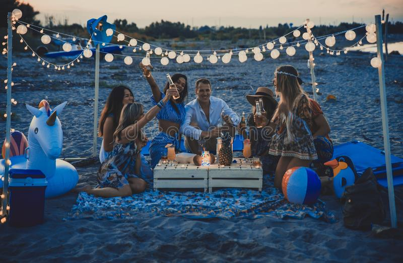 Group of friends making party on the beach at sunset time royalty free stock photo