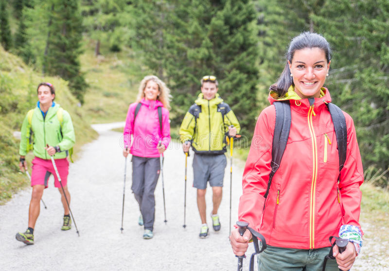Group of friends making trekking excursion in the forest royalty free stock image