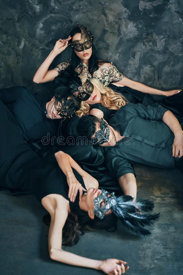 Group of friends in masquerade carnival mask sitting on floor relax after party stock photo