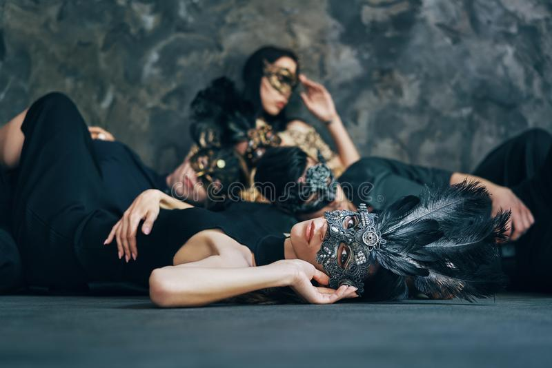 Group of friends in masquerade carnival mask sitting on floor relax after party royalty free stock photo
