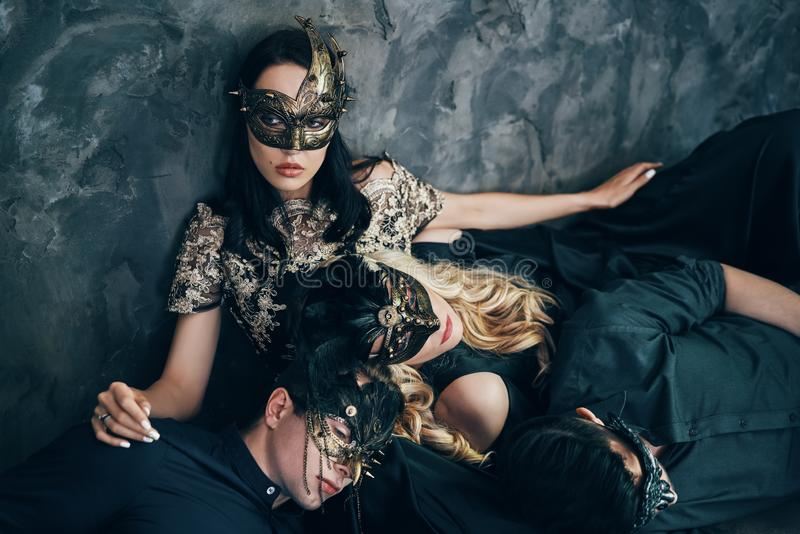 Group of friends in masquerade carnival mask sitting on floor relax after party stock photos
