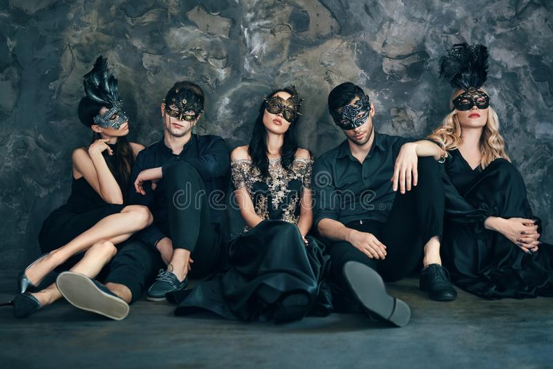 Group of friends in masquerade carnival mask sitting on floor relax after party stock image