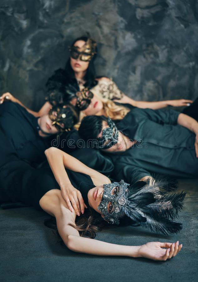 Group of friends in masquerade carnival mask sitting on floor relax after party royalty free stock photography