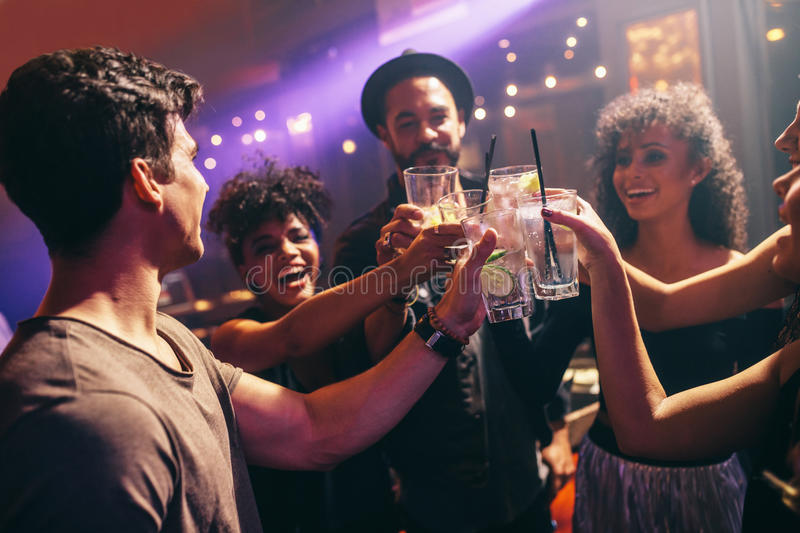 Group of friends at nightclub celebrating with drinks stock photos
