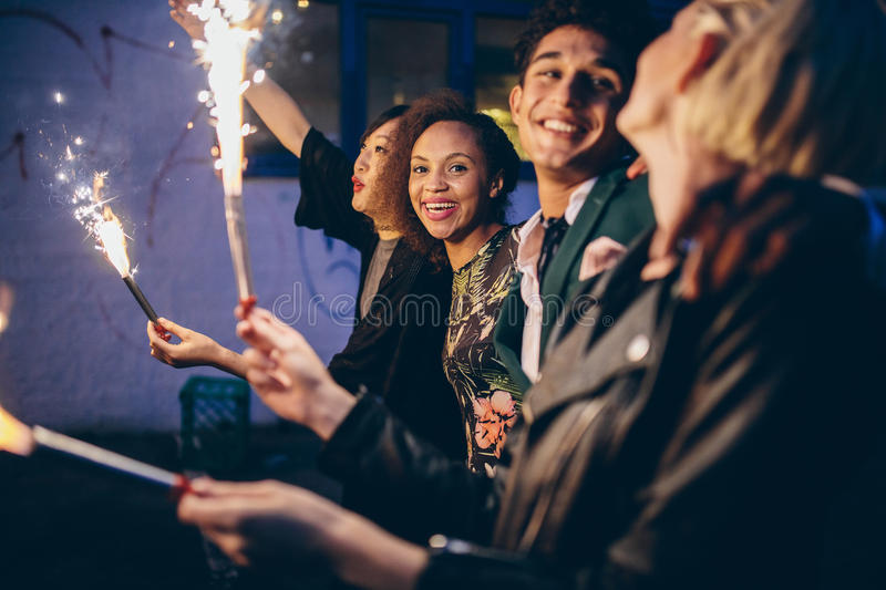 Group of friends partying and enjoying out with sparklers. Group of friends enjoying out with sparklers. Young men and women enjoying new years eve with stock image