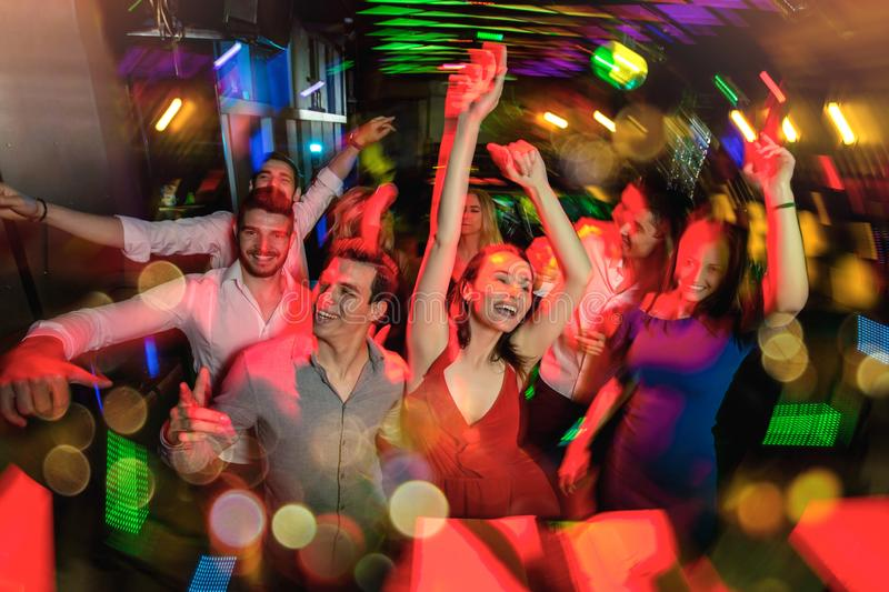 Group of friends partying in a nightclub royalty free stock image