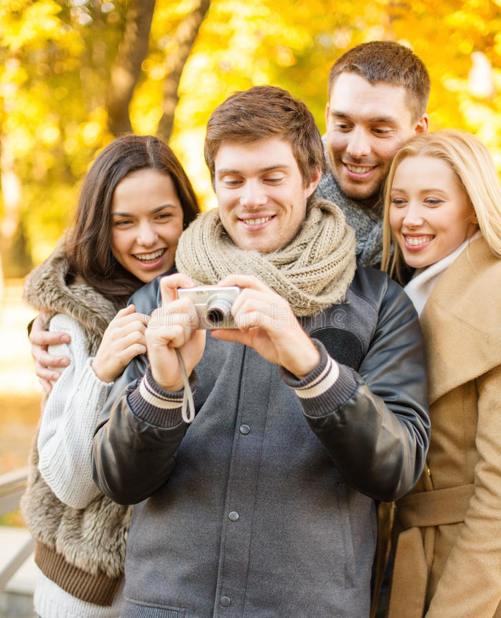 Download Group Of Friends With Photo Camera In Autumn Park Stock Photo - Image: 34774708