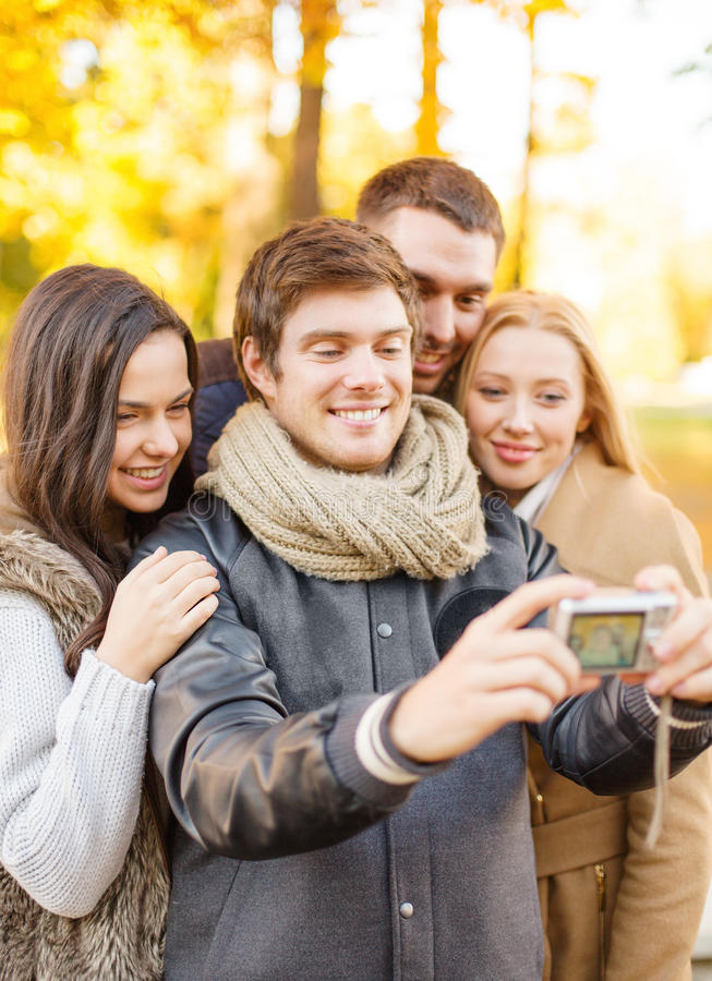 Group Of Friends With Photo Camera In Autumn Park Royalty Free Stock Images