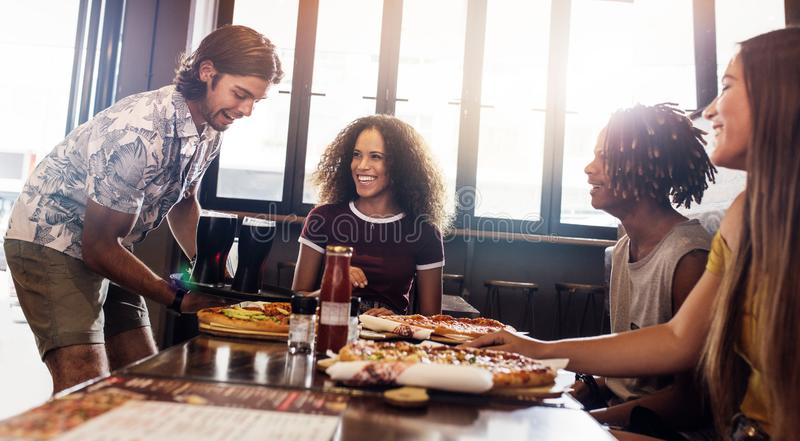 Group of friends at pizza restaurant royalty free stock image
