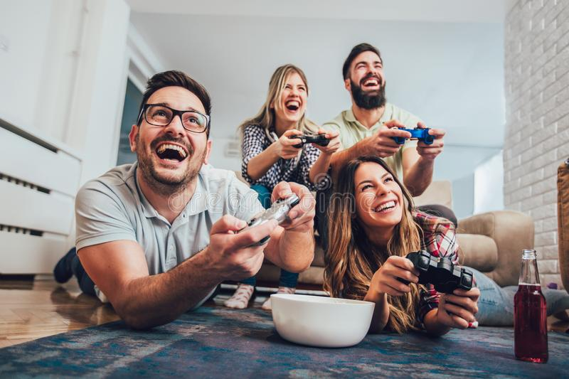 Group of friends play video games together at home. Having fun royalty free stock photography