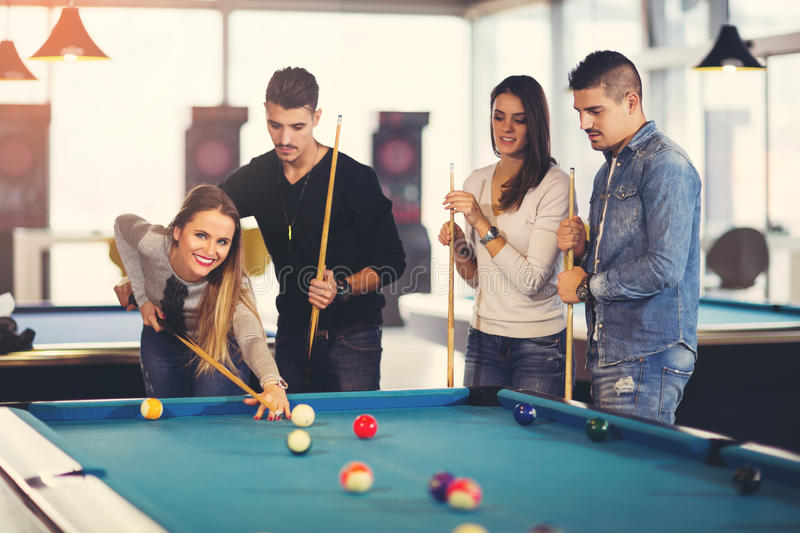 Group of friends playing billiard. Group of young friends playing billiard stock image