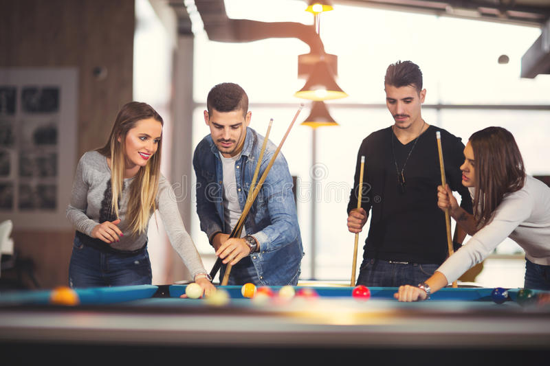 Group of friends playing billiard. Group of young friends playing billiard stock images