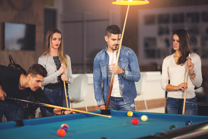 Group of friends playing billiard. Group of young friends playing billiard stock photo