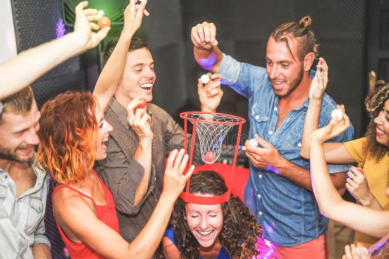 Group of friends playing funny basketball games inside a pub cocktail bar - Young happy people having fun hangout in the weekend. Friendship, entertainment stock photo