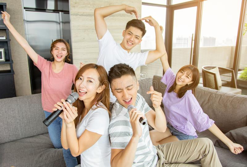 Group of friends playing karaoke at home royalty free stock image