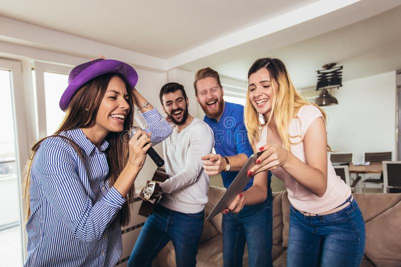 Friends playing karaoke at home. Concept about friendship, home entertainment and people royalty free stock photography