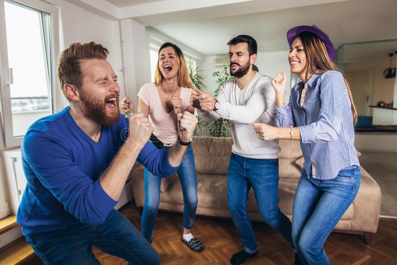 Friends playing karaoke at home. Concept about friendship, home entertainment and people stock photos