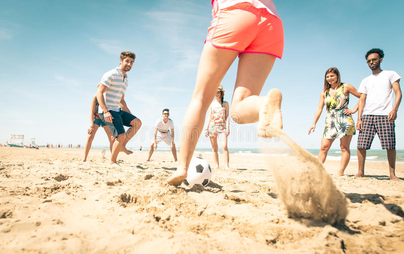 Group of friends playing soccer on the beach royalty free stock photos