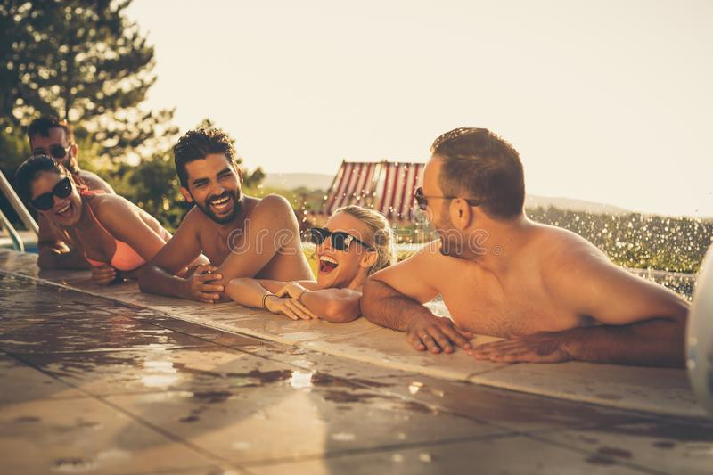 Friends having fun at the pool. Group of friends at a poolside summer party,  having fun in the swimming pool, splashing water and laughing stock photos