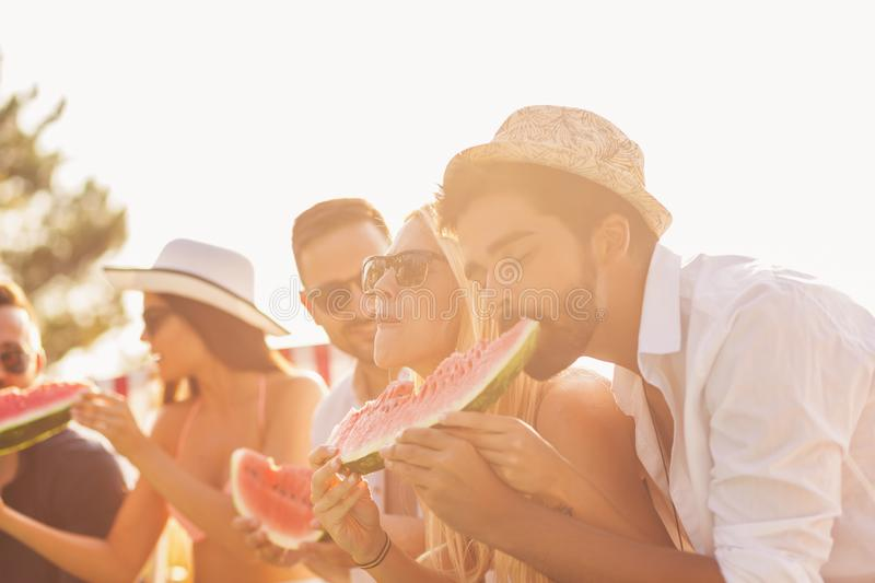 People eating watermelon. Group of friends at a poolside summer party, sitting at the edge of a swimming pool, eating cold watermelon slices and having fun royalty free stock images