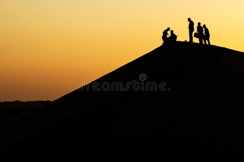 Group of friends practicing sand surf on top of a dune in the desert of Abu Dhabi with sunset and silhouettes stock photo
