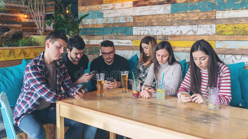 Group of friends at pub ignoring each other in favour of mobile phone royalty free stock images