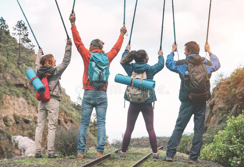 Group of friends raising hands up holding trekking poles on a peak of mountain - Young people exploring the nature stock photo