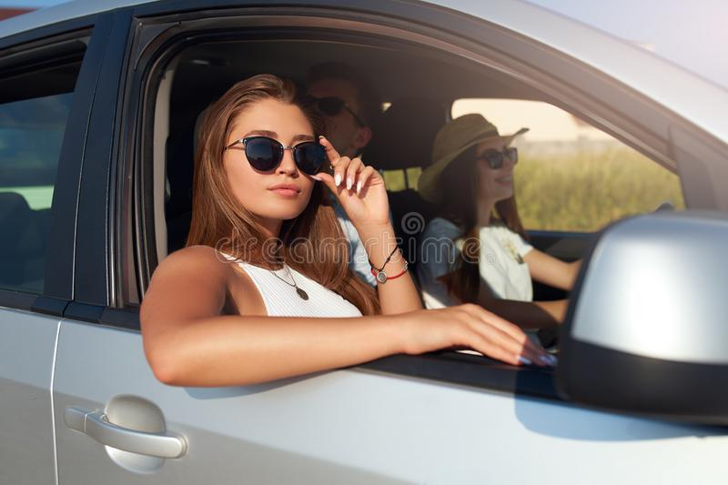 Group of friends rented a car on summer road trip and arrived to the sea beach. Woman in glasses looks out of the car stock images