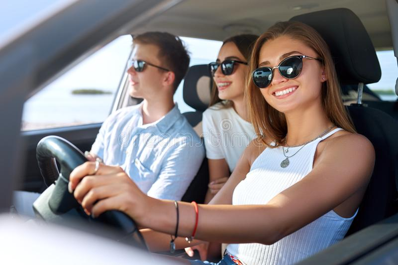 Group of friends rented a car on summer road trip and arrived to the sea beach. Girl having fun with friends in vehicle stock image