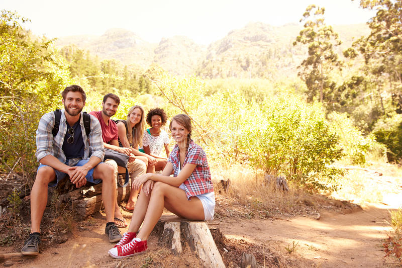 Group Of Friends Resting On Walk Through Countryside stock images
