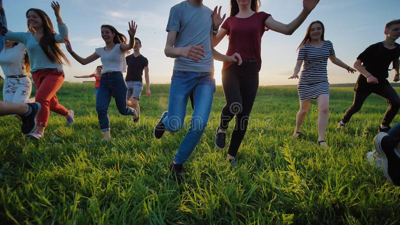 Group of friends running happily together in the grass stock images